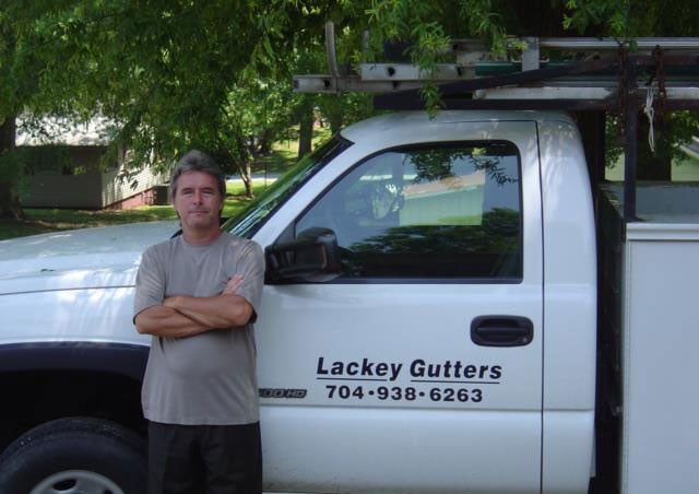 Owner of Lackey Gutters on a job site ready to install new gutters for a client